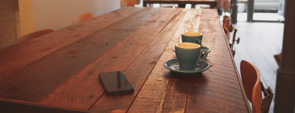 wooden table in a cafe with a deserted iphone and two coffee cups